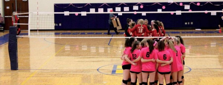 The WHHS Women's Volleyball team huddles during the Volley for the Cure game. The Lady Eagles are 6-10 this season.