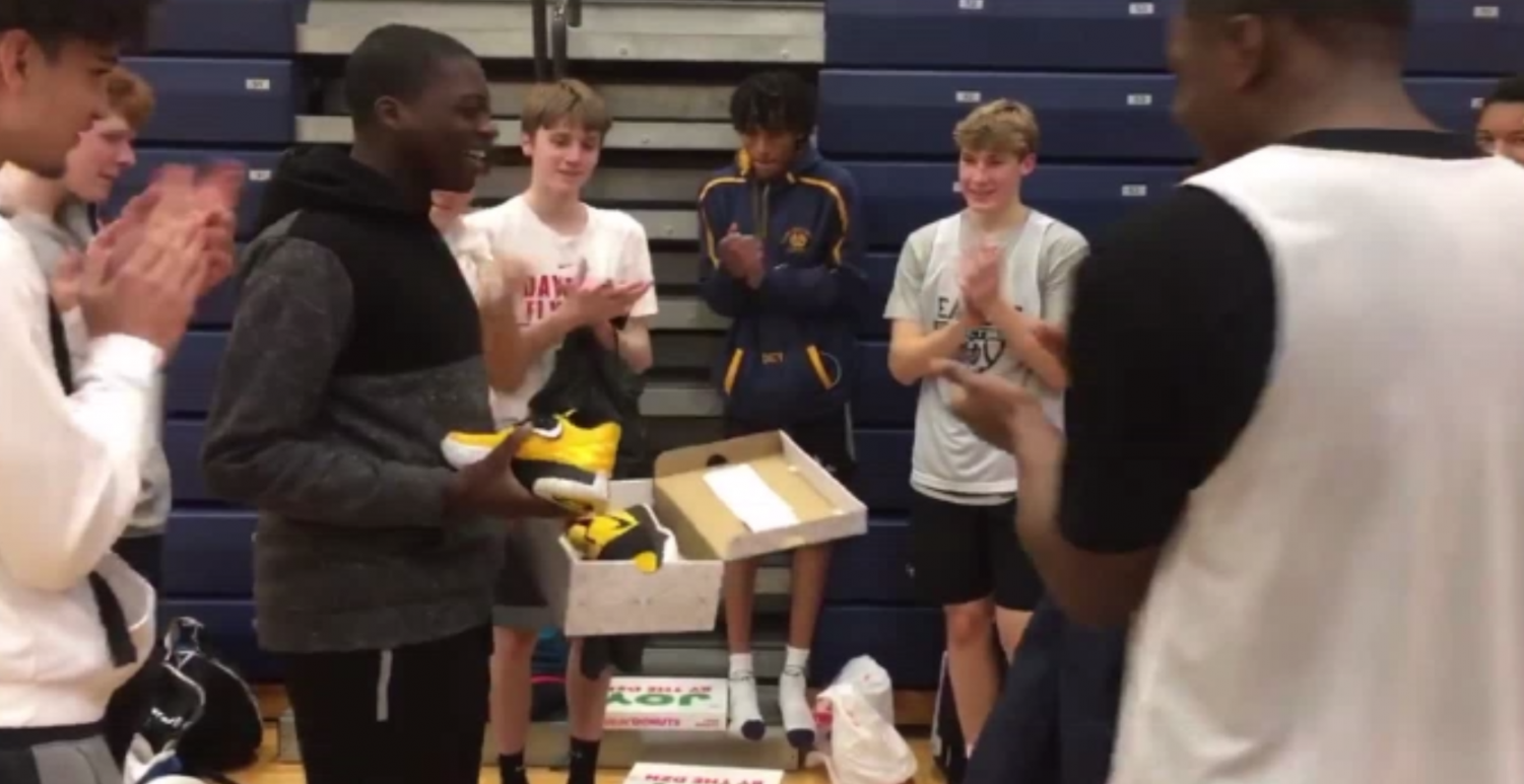 Team manager SENIOR David Akanbi is seen surrounded by his teammates after being presented with his gift from the team. Max Poynter, '22, had the idea to raise money for the new shoes.