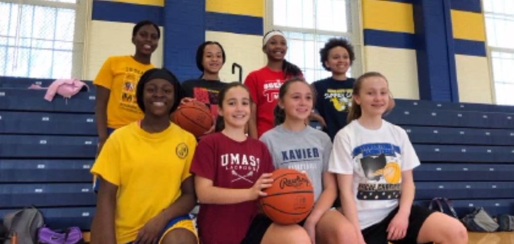 Girls junior high basketball players stand with a basketball in front of the bleachers in the Junior High Gym, with eighth graders in the back row and seventh graders in the front row. The girls' junior high basketball teams have games throughout the week.