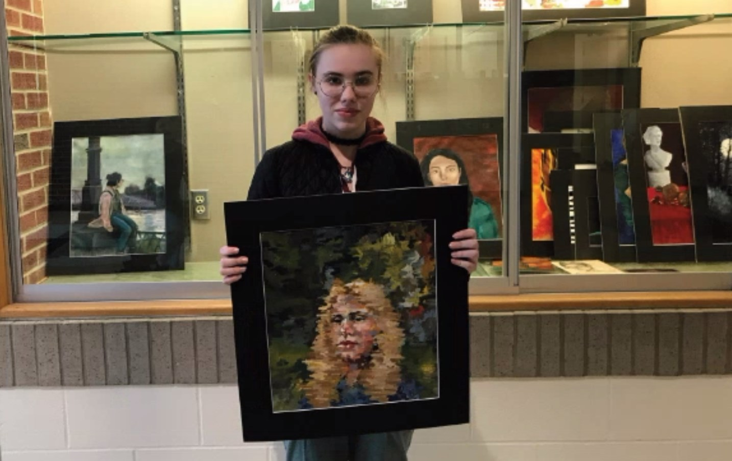 Alexandra Franz, '23, poses with her favorite piece from the Scholastic Art Awards. Franz received 19 awards for her work.