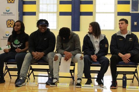 Our photo of the day shot by SENIOR Jonathan Brown showcases five of the ten seniors who signed to colleges this week for athletics. From the left, Alysea Jenkins signed to Roosevelt University for basketball, Ryan Mickens to Mount ST Joseph for football, Caleb Streat will be playing football for Tiffin University, and finally Augustana College will be welcoming Dominique Valentine and Isaiah Valentine (far right) for swimming. Congratulations to our seniors advancing their academic and athletic educations!