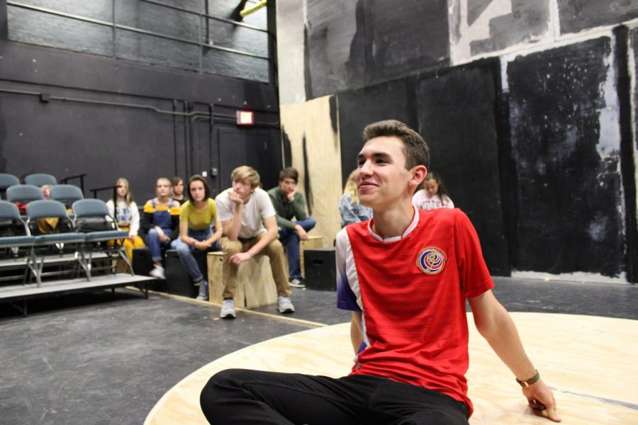 Jack Giglia, '21, listens intently as director Michael Sherman gives advice on how to better connect to his character, Christopher. Meanwhile, the ensemble watches in the wings, as they do throughout they show, occasionally moving set pieces around the stage.
