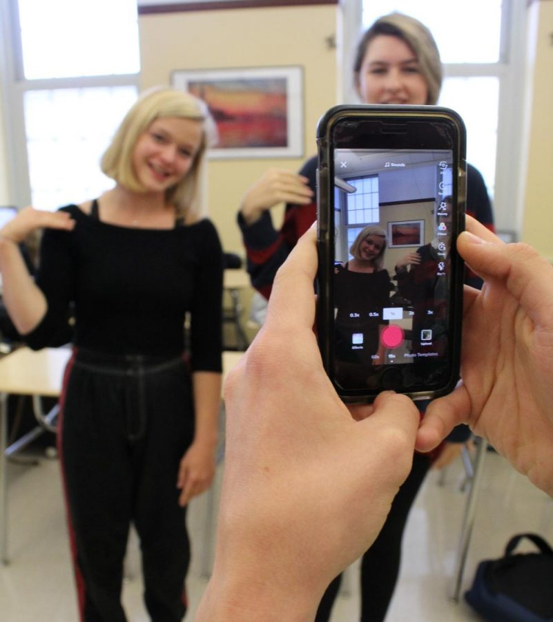 SENIORS Alma Russell and Cat Henning practice a popular dance from the app Tik Tok while SENIOR Elliot Hull frames the shot. Tik Tok has taken WHHS by storm, with several students gaining thousands of likes each day.