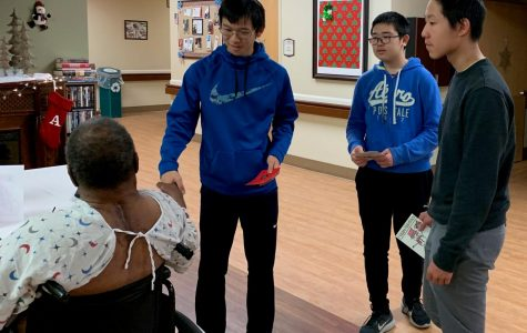 From left to right: Red Cross Club members Justin Chan, '22, Ben Liu, '22, and Bojun Fu, '22, shake hands with a veteran patient during their visit to the Veteran Association Medical Center.