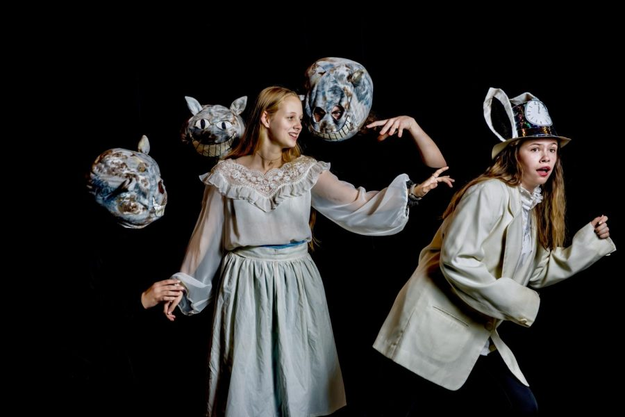 Alice, played by Kaelyn Karr '24, is surrounded by the three Cheshire Cats while curiously reaching for the White Rabbit, who is played by Ella Shaffer '25.