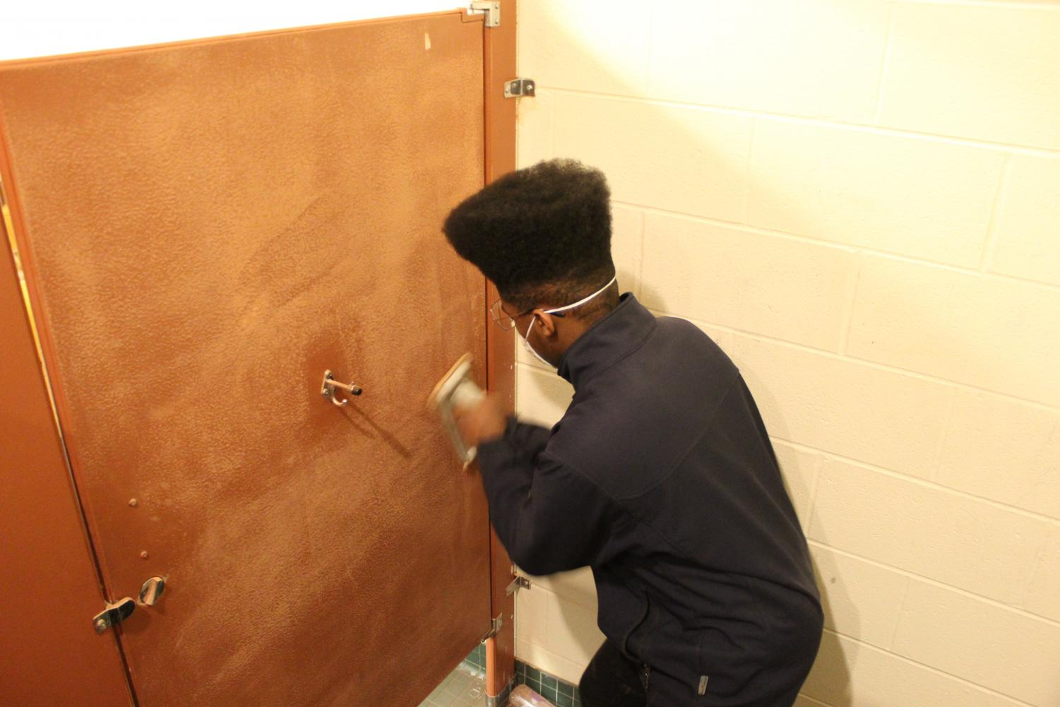 Micah Ballard, '21, vigorously sands the inside of a stall in preparation for decorating. Art club members hope this will not only beautify the school, but also discourage vandalism.
