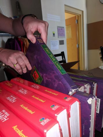 A student lifts a Latin textbook off of a shelf. Although many at WHHS lament the three-year Latin requirement, club writer, Otto Kindel, argues that it is a valuable aspect of WHHS