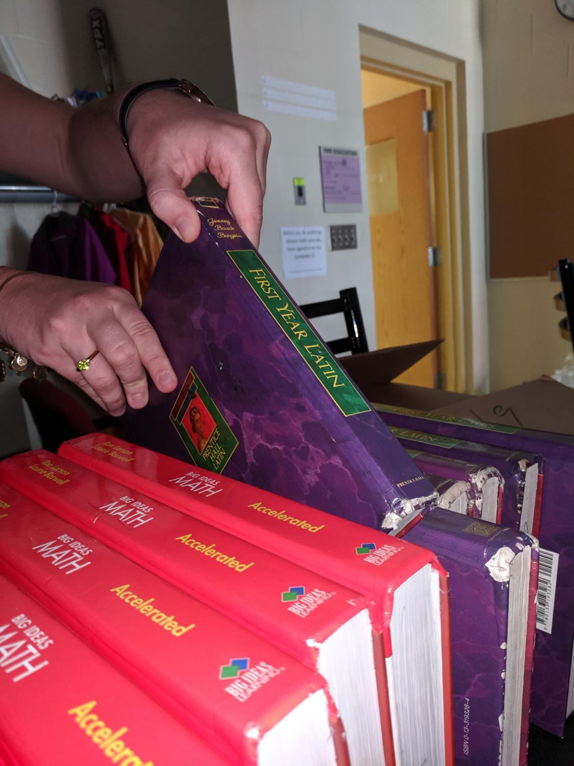 A student lifts a Latin textbook off of a shelf. Although many at WHHS lament the three-year Latin requirement, club writer, Otto Kindel, argues that it is a valuable aspect of WHHS' Classical education.