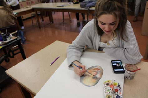 "Alexandra Franz, '23, works on a self portrait during her AP Studio Art class, using a selfie for reference. Franz worked in watercolor, which she developed as her specialty this year. ""A lot of people think [watercolor is] hard, but there's a wildness to it that is fun to try to tame that I really enjoy,"" Franz said."
