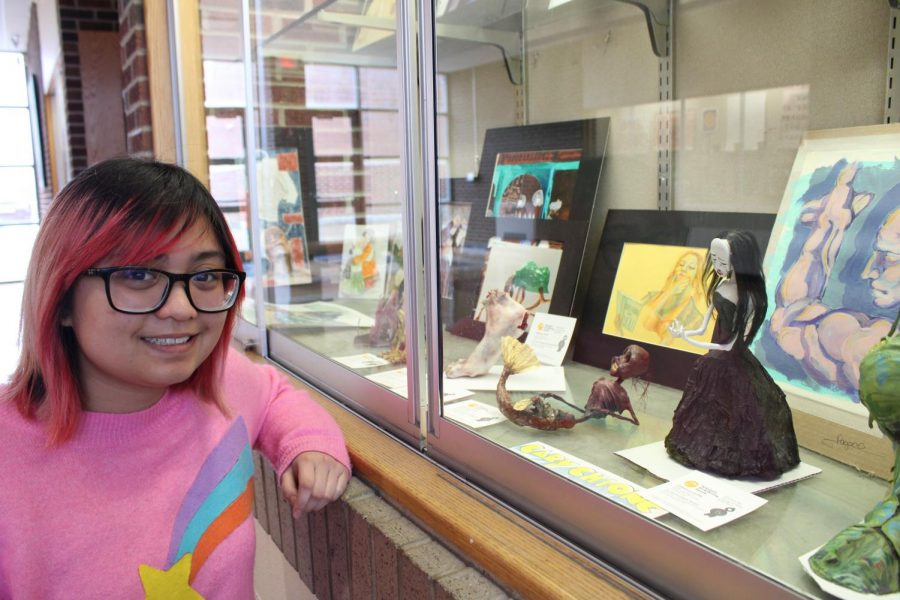 SENIOR Gaby Chiong poses next to the sculptures she entered into the Overture Awards, currently on view in the Arts and Science building. As a finalist, her art, based on well-known fairy tales, will be on display in the Aronoff Center's Center Stage Room from March 3 to 7.