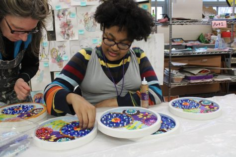 Honora Martin, '23, works alongside artist Suzanne Fisher to put together one of the 10 inch mosaics. Martin uses Art Club as an outlet for her creativity, and she appreciates the chance to use art to make others feel better.