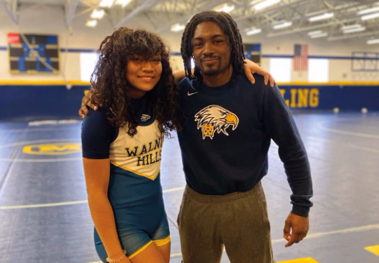 Wrestler Erin Martin, '22, standing with her coach, Matt Lindsay, after winning her first match at Moeller. Martin defeated a male opponent from Anderson High School.
