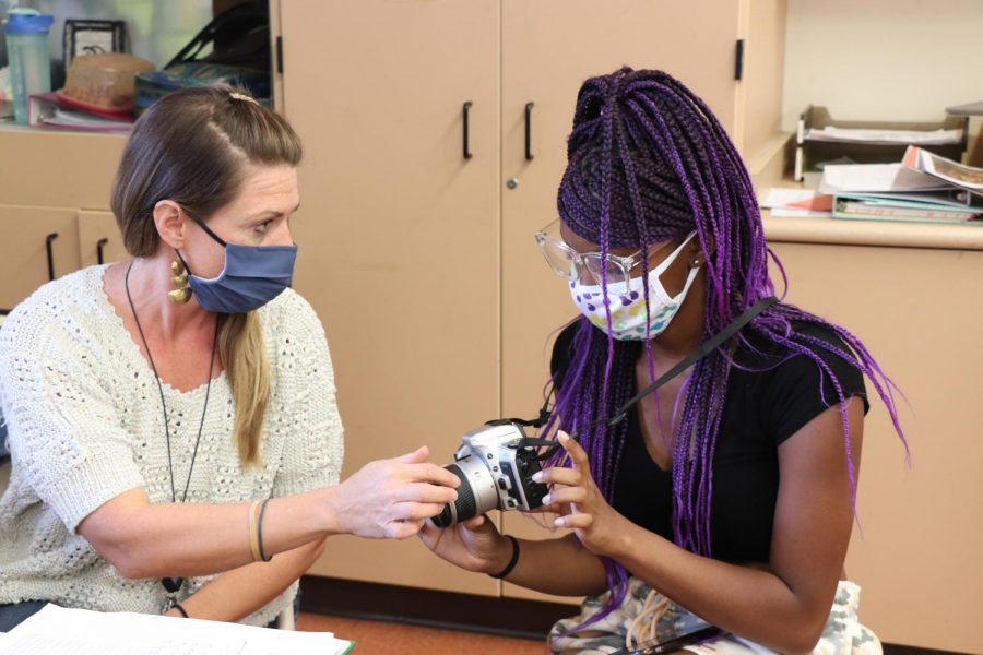 Photography teacher Elizabeth Knodle teaches Serentiy Billups '24 the basics of photography to start the year off. Knodle is excited to watch her students develop their very first roll of film in the weeks to come.