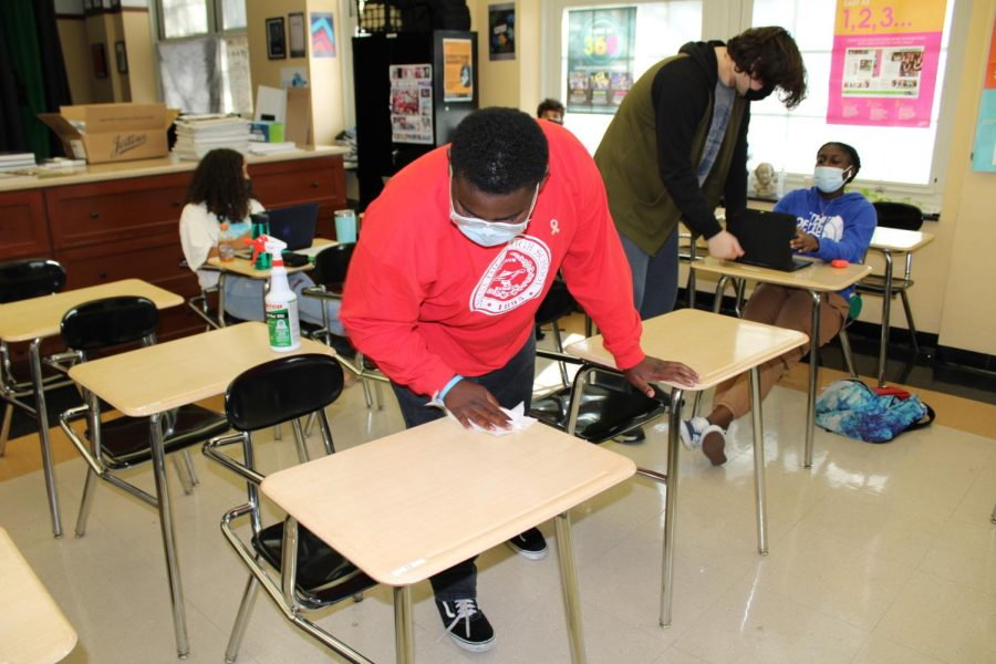 Alonzo Montgomery '23, exhibiting covid protocol procedures, by cleaning off the desks of his classroom.