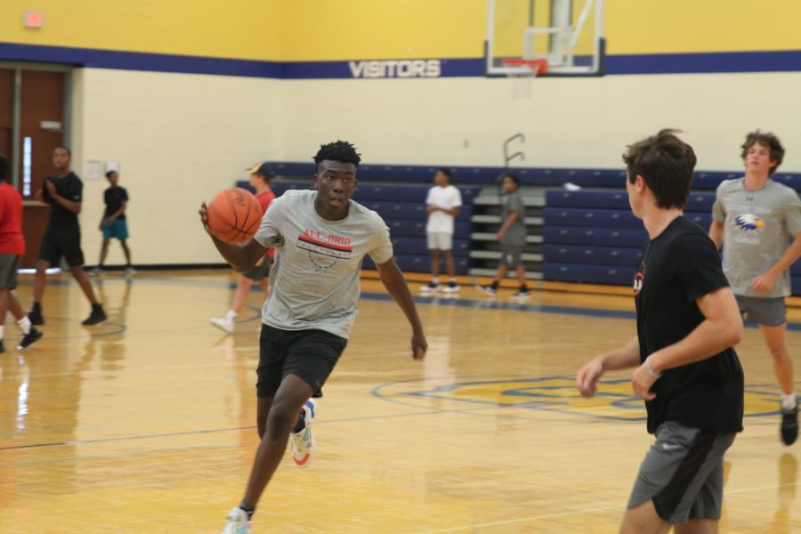 McKinely drives towards the basket during an open gym at Walnut. College coaches from universities across the country have been dropping in to watch the WHHS players at the open gyms.